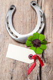 Horseshoe and four leaf clover with empty tag Stock Image