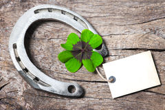 Horseshoe and four leaf clover Stock Photos