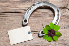 Horseshoe and four leaf clover with empty tag Royalty Free Stock Image