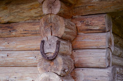 Horseshoe hang on log house corner. Luch symbol Royalty Free Stock Photography