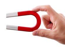 Horseshoe magnet. Holding a horseshoe magnet against a white background Royalty Free Stock Photo