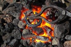 Horseshoe and pliers. Blacksmithing, heating of the metal horseshoes on coals Royalty Free Stock Photos