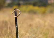 A horseshoe. A rusted horseshoe hanging on a metal pole in a meadow stock photos