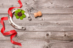 Horseshoe, shamrock and champagne cork on old wooden Royalty Free Stock Photos