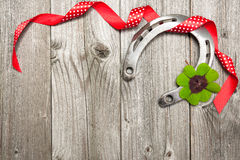 Horseshoe, shamrock and red ribbon on old wooden Royalty Free Stock Image