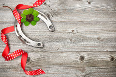 Horseshoe, shamrock and red ribbon on old wooden Royalty Free Stock Photos