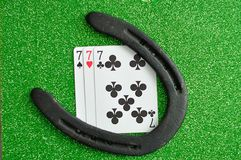 A horseshoe and three number seven cards. On a green background Stock Photo
