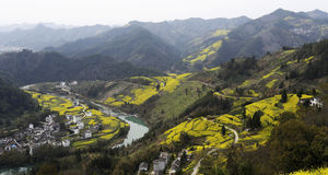 Horseshoe and u-shaped river in the mountains, the village and yellow rape, on opposite sides of the river Royalty Free Stock Photo