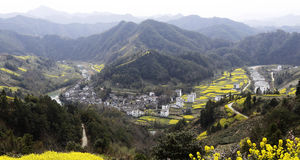 Horseshoe and u-shaped river in the mountains, the village and yellow rape, on opposite sides of the river Stock Photos