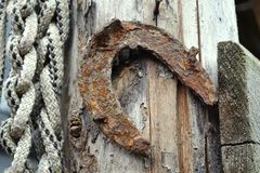 Horseshoe on wooden door with a rope royalty free stock photography
