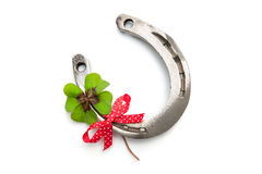 Horseshoes and clover with four leaf Stock Photos