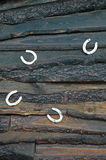 Horseshoes on the wall. Horseshoes on the charred wooden wall stock image