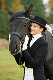 Horsewoman jockey in uniform with horse. Horsewoman jockey in uniform standing with horse outdoors Royalty Free Stock Photography