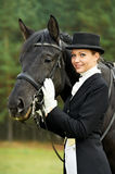 Horsewoman jockey in uniform with horse. Horsewoman jockey in uniform standing with horse outdoors Stock Images