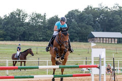 Horsewoman during the jump-off Stock Images