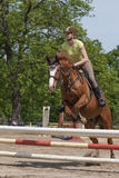 Horsewoman is jumping. Vertically. Stock Photography