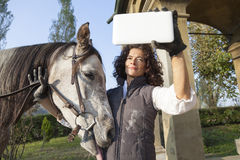 Horsewoman takes a selfie with his horse. To the country roads in autumn Royalty Free Stock Photos