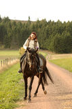 Horsewoman on tittup horse on country roads. Royalty Free Stock Photo