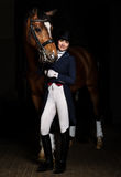 Horsewoman in uniform with a brown horse in the stable. Stock Image