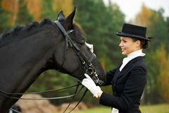 Horsewomanjockey in der Uniform mit Pferd Stockbilder