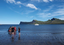 Horsntrandir, nature reserve, Iceland. Bird observers and hikers landing, with Hornbjarg one of the world largest bird cliff in the background Royalty Free Stock Photography