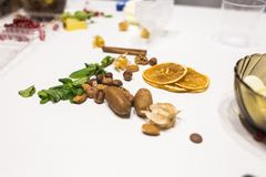 A hortelã, as porcas, a canela e as laranjas secadas encontram-se em uma tabela branca na cozinha imagem de stock royalty free