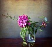 Hortensia en el florero de cristal con las flores salvajes Foto de archivo