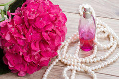 Hortensia  flowers and bottle of fragrance. Pink hortensia  flowers and bottle of fragrance Royalty Free Stock Images