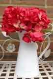 Hortensia rouge artificiel dans la cruche blanche photo libre de droits