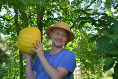 Horticulturist showing a pumpkin Stock Images