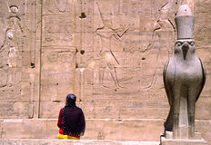 Horus temple in Edfu Egypt. Horus temple in Edfuh Egypt with woman with veil and at wall hieroglyphics stock image
