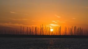 Horyzontalna fotografia półmrok Wieczór niebo pomarańczowego kolor i few chmury Słońce jest pobliskim horyzontem Wiele statki z s zdjęcie stock