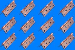 Horyzontalni rzędy metalu brązu drzwiowi zawiasy na błękitnym tle zdjęcia royalty free
