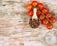 Horyzontalny karmowy sztandar z dojrzałymi czerwonymi czereśniowymi pomidorami i peppercorns na drewnianym tle Opróżnia przestrze Fotografia Stock