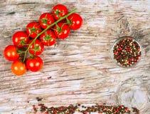 Horyzontalny karmowy sztandar z dojrzałymi czerwonymi czereśniowymi pomidorami i peppercorns na drewnianym tle Opróżnia przestrze Zdjęcia Stock