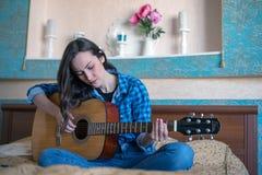 Horyzontalny modniś dziewczyny portret z gitarą akustyczną bawić się na łóżku Fotografia Stock