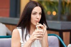 Horyzontalny plenerowy strzał rozważna atrakcyjna kobieta cieszy się dzień wolnego, pozy w plenerowej kawiarni, napoju milkshake, obraz royalty free