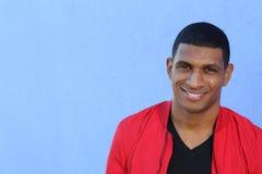 Horyzontalny portret przystojny młody afrykański mężczyzna ono uśmiecha się na błękitnym tle Fotografia Royalty Free