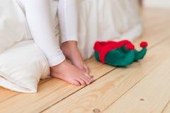 Horyzontalny strzał unrecognizable mali mali dziecko stojaki na drewnianej podłoga z elfem s kuje, siedzi na białych bedclothes, zdjęcie royalty free