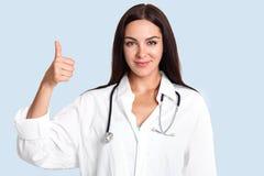 Horyzontalny strzał zadowolona kobiety lekarka utrzymuje kciuk podwyżki lub daje zgodzie, aprroves, jest ubranym białego medyczne fotografia royalty free