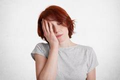 Horyzontalny strzał zmęczona zanudzająca kobieta z krótką fryzurą, zakończenia ono przygląda się i pokrywy stawiają czoło z ręką  obrazy stock