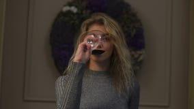 Horyzontalny widok ładna blond dziewczyna pije wino przy tłem Bożenarodzeniowy wianek zbiory