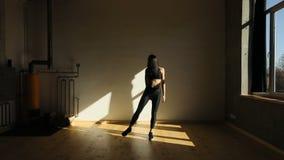 Horyzontalny widok atrakcyjny sportwoman podnosi nogę w sprawności fizycznej studiu na boku zbiory