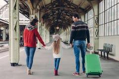 Horyzontalny widok czule rodzice i ich dauhter utrzymanie wręcza wpólnie, iść mieć wycieczkę za granicą, poza na stacji kolejowej zdjęcie stock