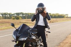 Horyzontalny widok elegancki ufny żeński rowerzysta ubierający w modnych ubraniach, siedzi na motocyklu, jest ubranym hełm, pokry zdjęcia stock