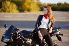 Horyzontalny widok rozważny rowerzysta stoi blisko ulubionego motocyklu, ubierającego w eleganckim stroju, kontemplacyjnego spojr zdjęcie royalty free
