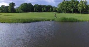 Horyzontalny widok sportowa kobieta jogging wzdłuż łąki blisko rzeki Poruszający tylny widok zdjęcie wideo