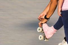 Horyzontalny widok Sprawdza łyżwy młoda dziewczyna przy łyżwiarka zdjęcie royalty free
