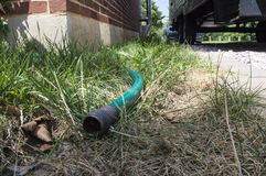 Hose laying out in grass in between house and driveway Royalty Free Stock Images