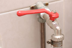 A hose plug quarter turn lever type ball valve water tap with red handle. Stock Photo